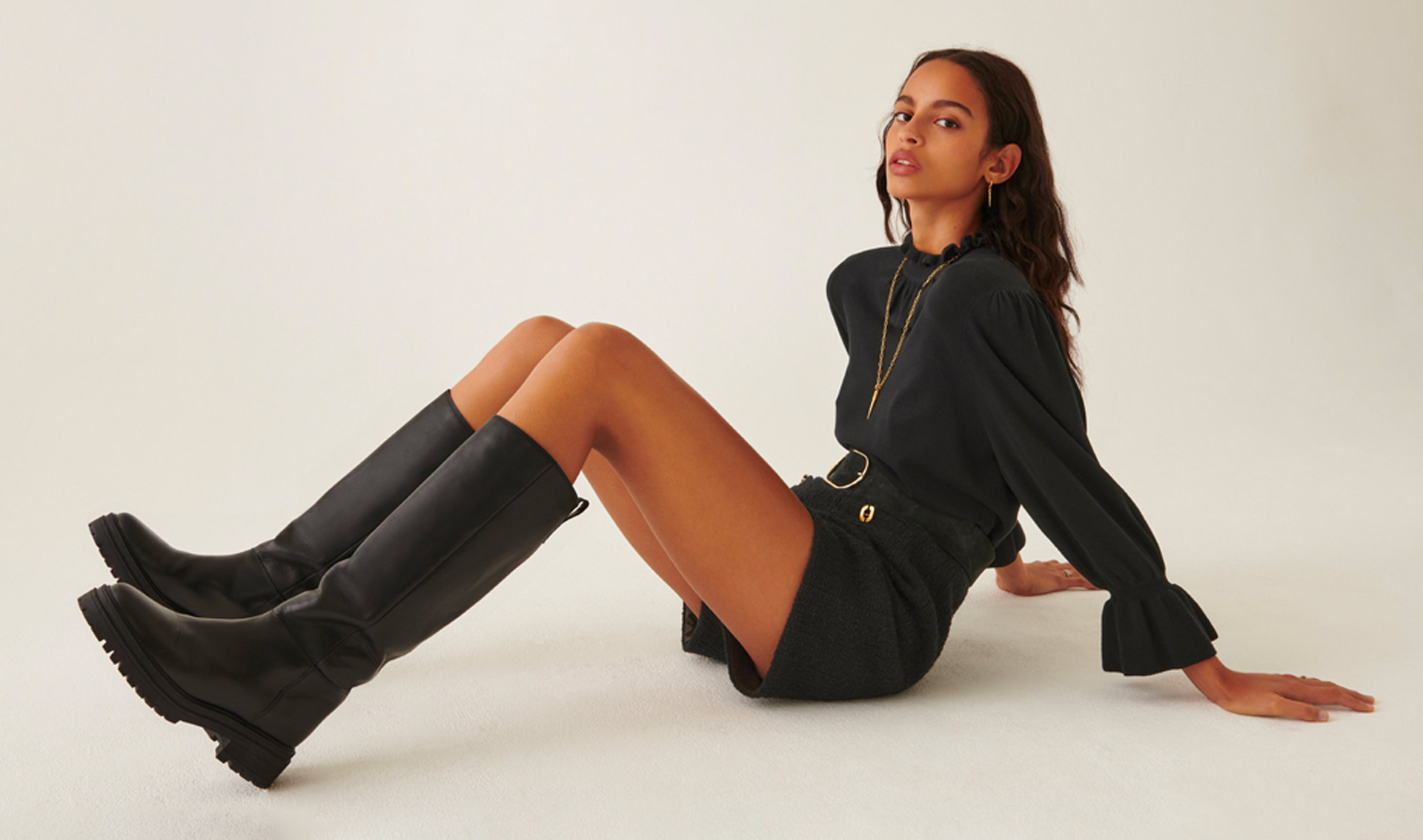 A brunette woman is wearing knee high leather boots from the ba&sh new boots collection