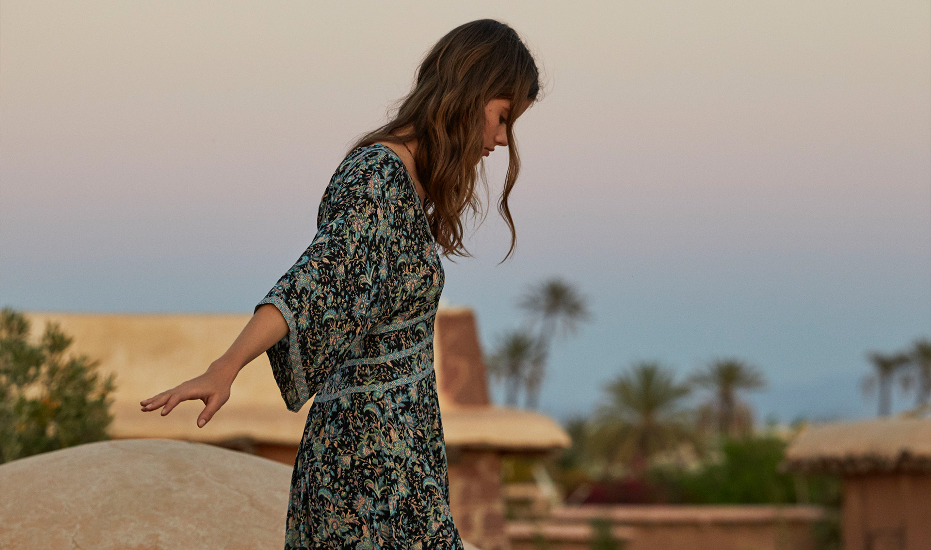 A woman walking, in the desert, wearing a printed backless maxi dress.