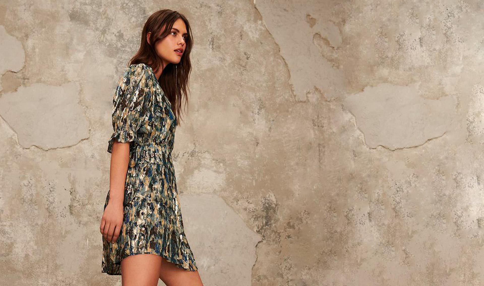 brown haired woman wearing a short blue printed dress with lurex