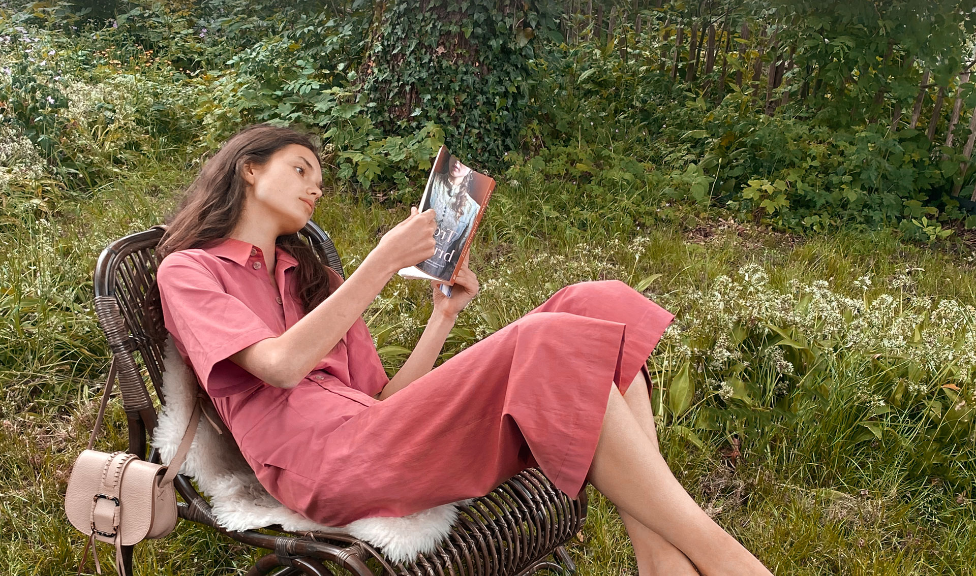 Woman wearing a pink overall, sitting on a chair in the garden, enjoying reading