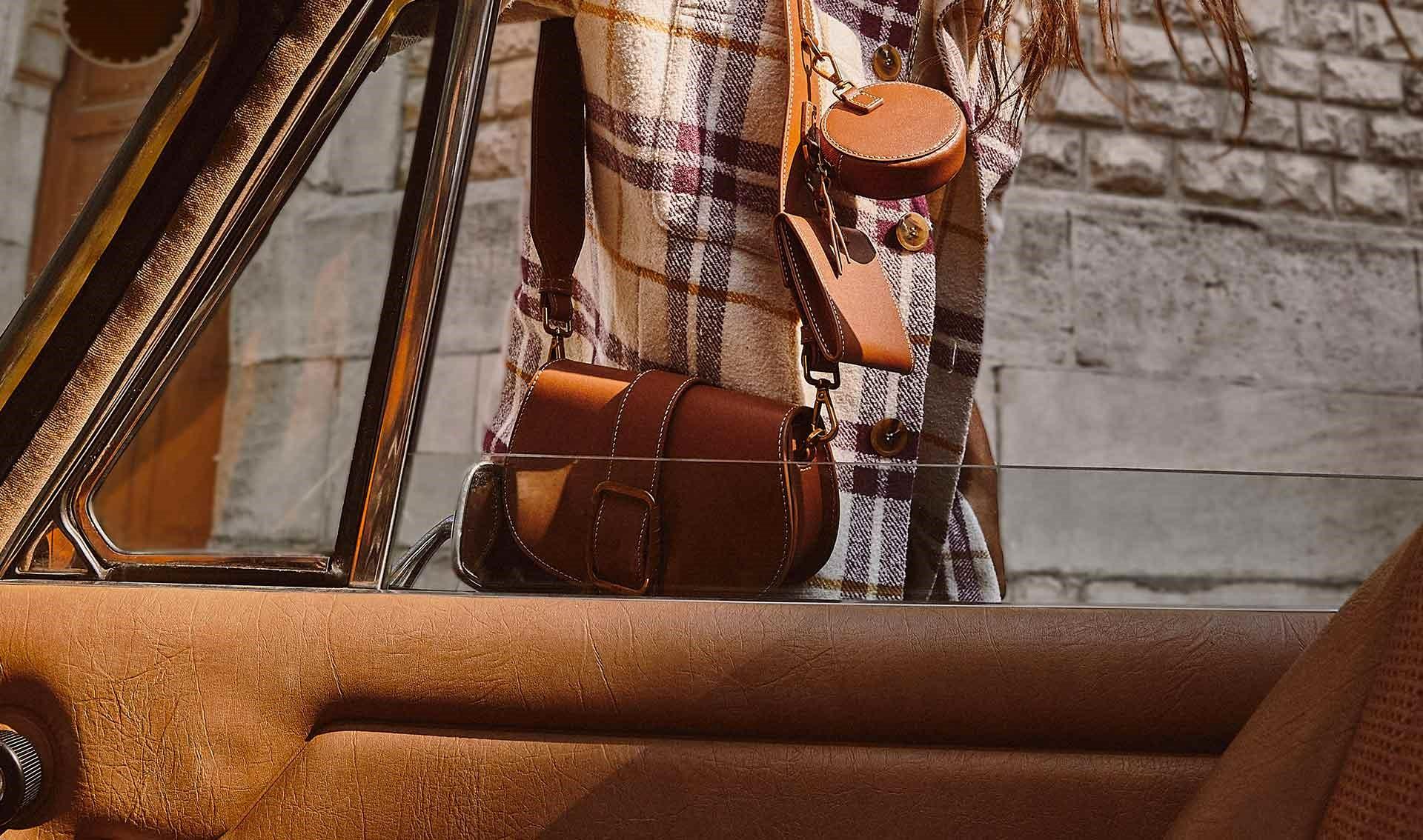 una mujer morena lleva una camisa a cuadros Ba&sh y una bolsa Teddy, modelo icónico bash, nueva colección bolsas