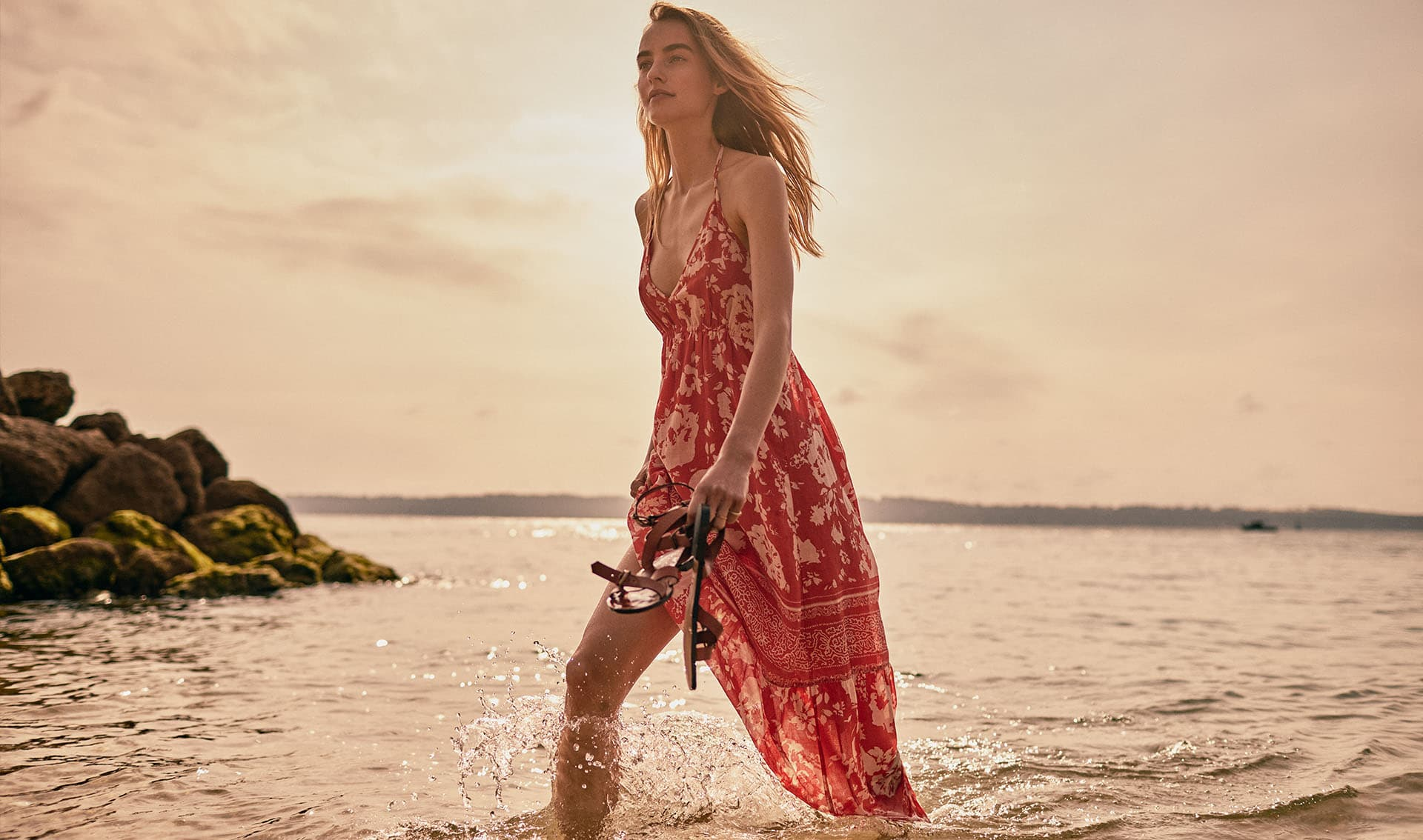 Girl walking on the shores of the sea wearing a long red printed dress and holding a pair of brown leather sandals in her hand.