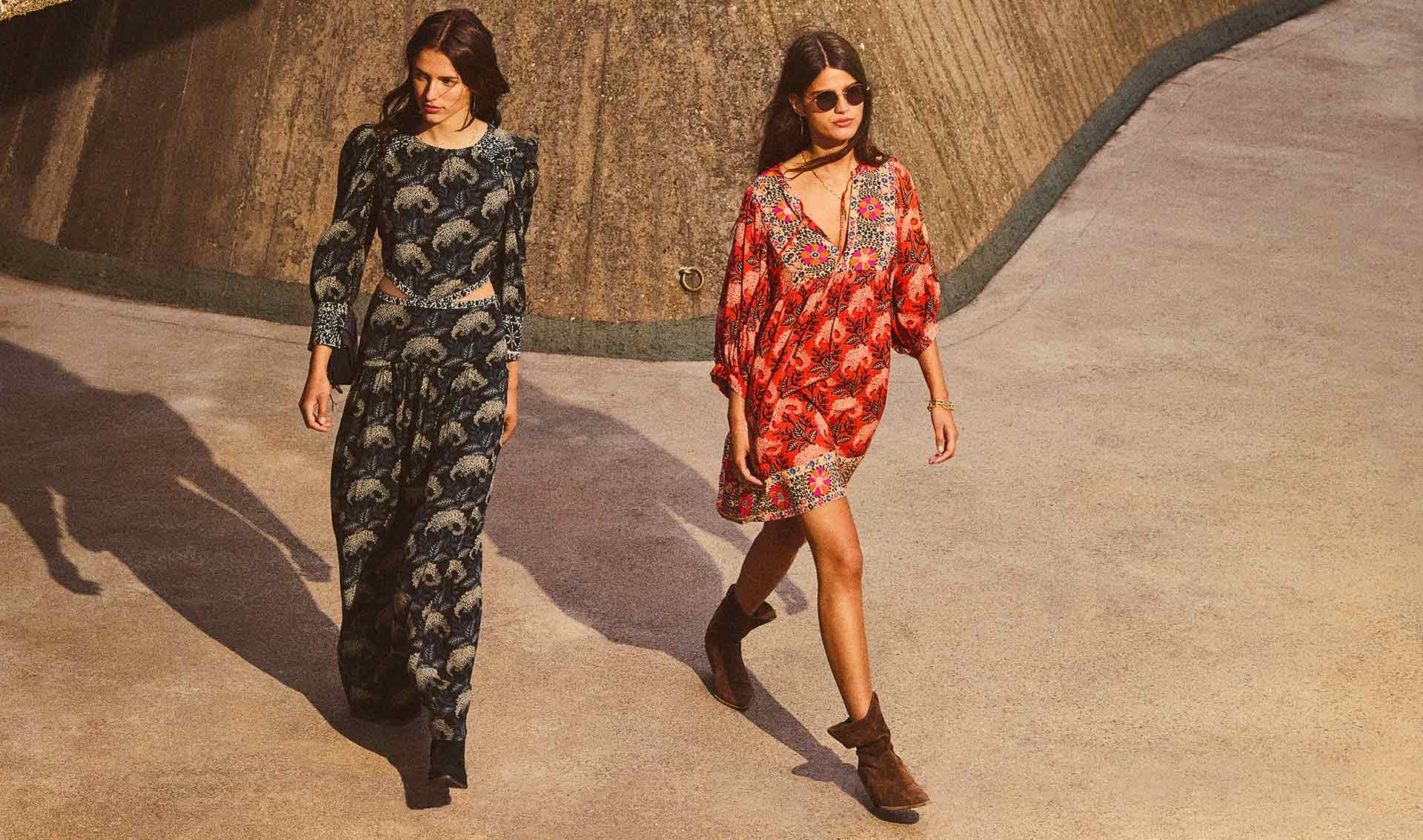 Two girls walking with printed dresses, one in a black printed dress with cutout detail and anotgher girl in a short printed orange dress.