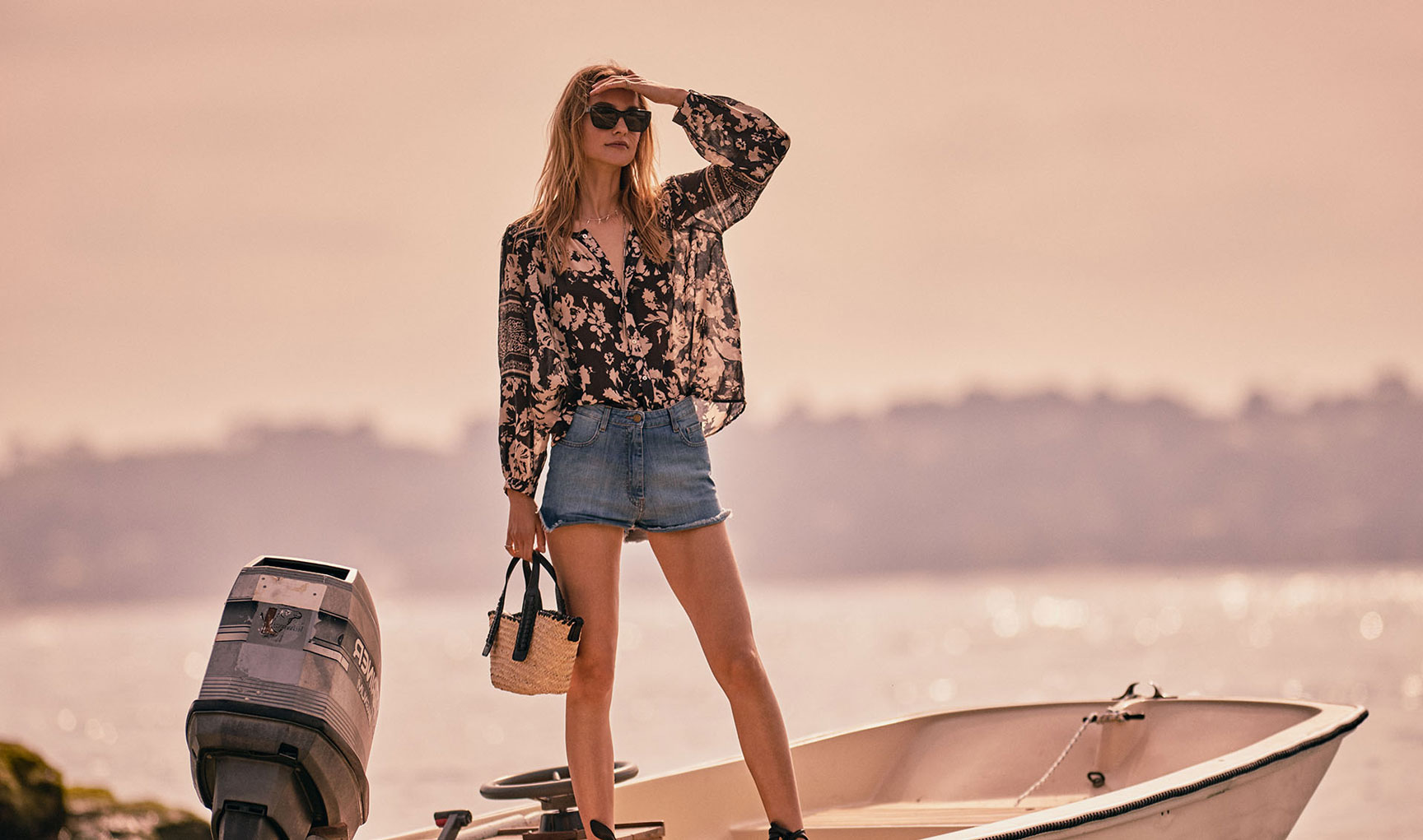 a woman on a boat, the sea, the beach, wearing a printed Ba&sh blouse, denim shorts, a wicker bag and sunglasses