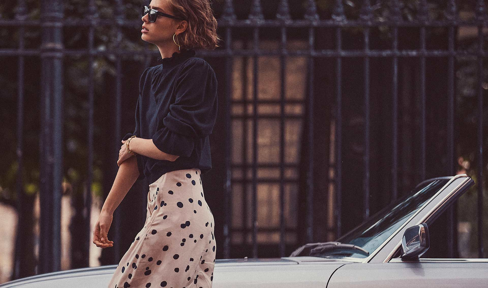 a woman with a white skirt with black polka dots, a sweater and ba&sh sunglasses