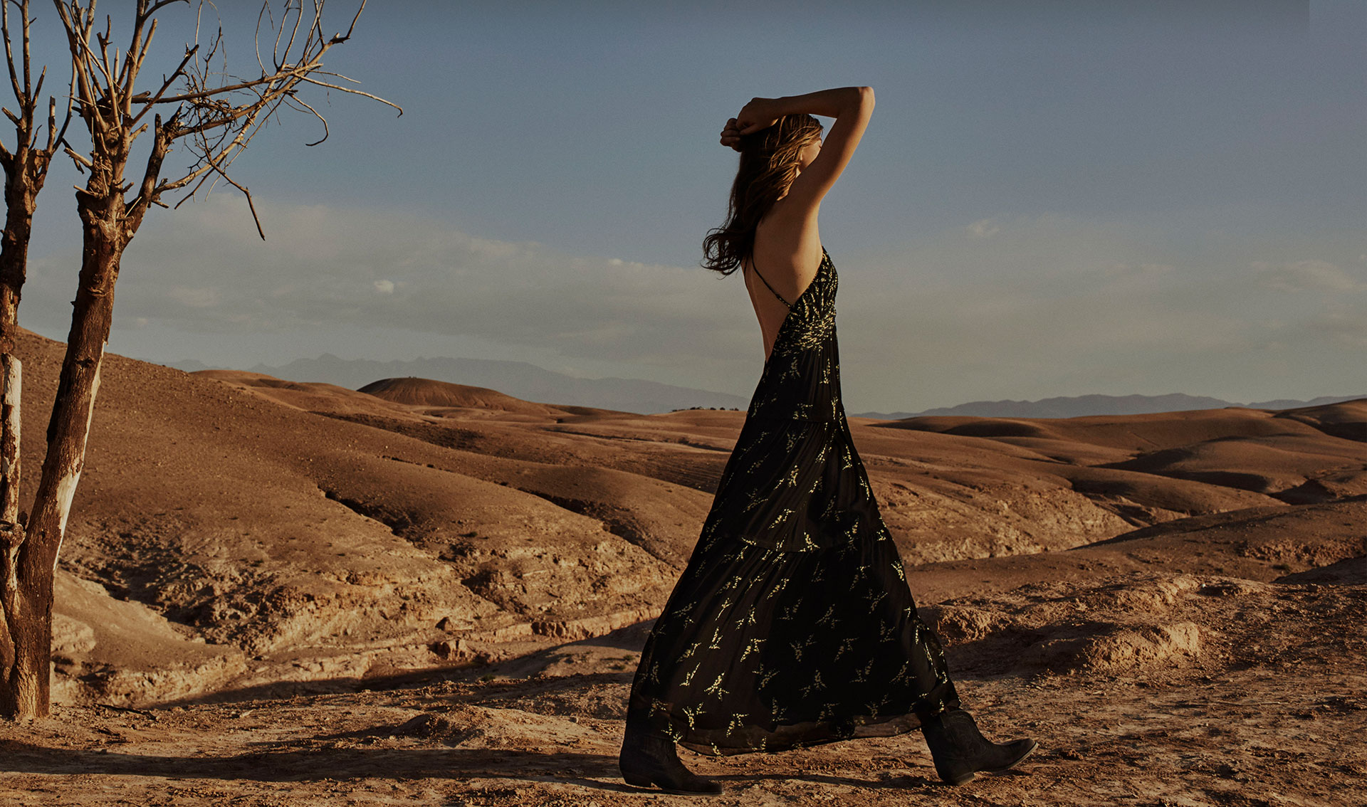 Woman walking in the desert, with a long printed backless dress