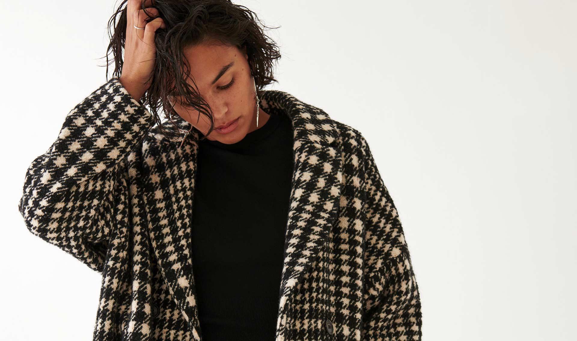 une femme brune porte un manteau à carreaux noir et blanc ba&sh, nouvelle collection hiver bash