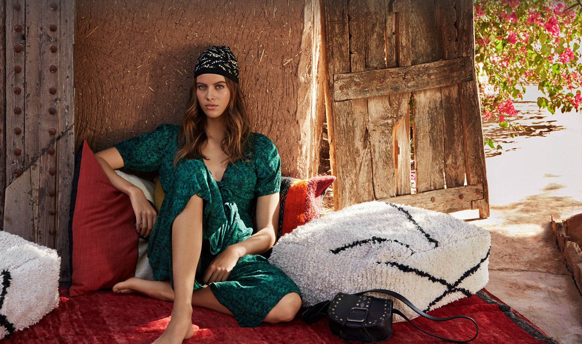 Woman sitting, in the heart of Marrakech city, wearing a green printed midi dress